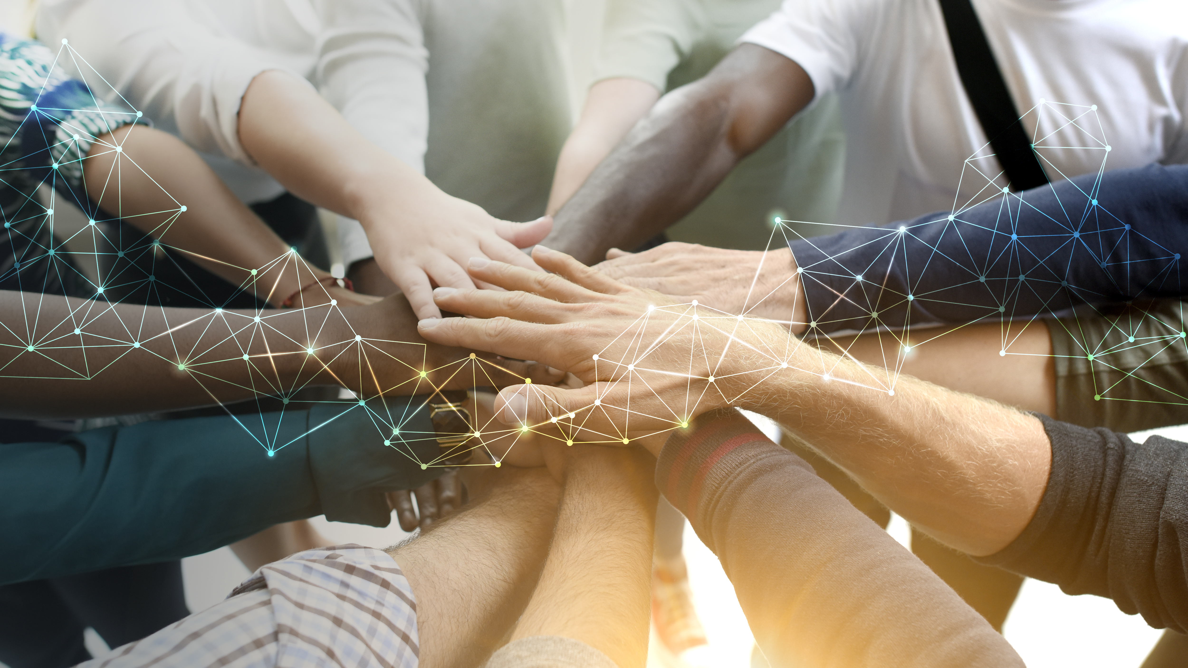 photo of a group of people putting their hands togehter as a sign of teamwork